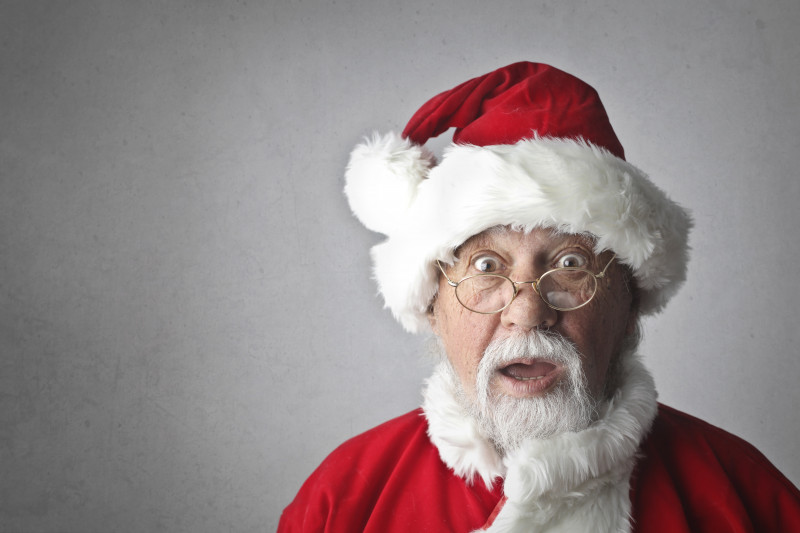 Close up of Santa wearing red hat with white fur trim against a white background