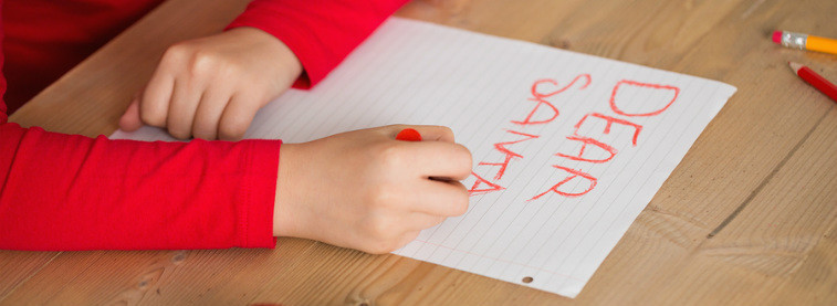 Close up of child writing a letter to Santa in red crayon