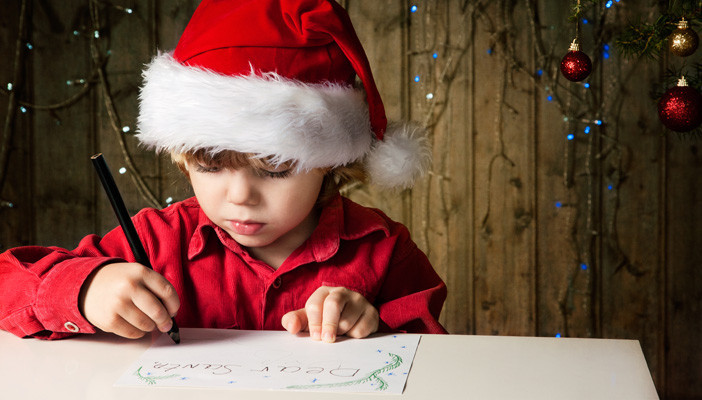 Young boy wearing Santa hat writing a letter to Santa