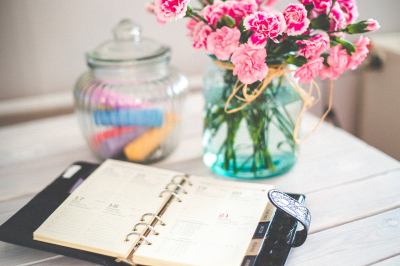 Organiser on a white table with a bunch of flowers