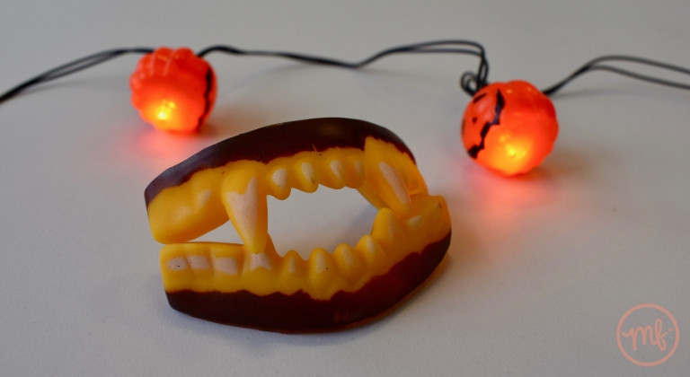 Close up of vampire teeth with pumpkin fairy lights in background