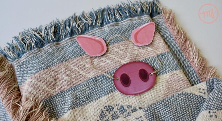 Cardboard pig snout and ears laid on a blanket