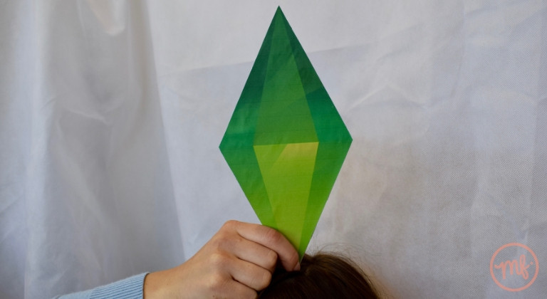 Hand holding a green Sim plumbob against a white background