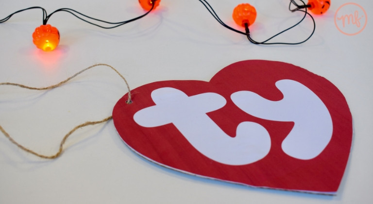 Carboard TY tag against a white background with pumpkin fairy lights