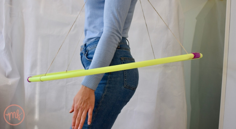 Woman wearing blue top and jeans with hula hoop hanging aroung attached with string