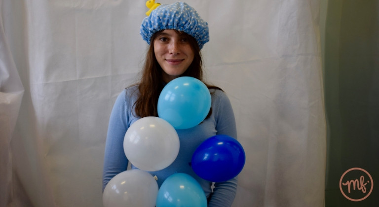 Woman with balloons stuck to body wearing a blue shower cap against a white background
