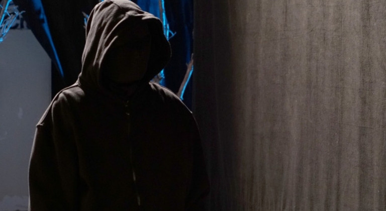 Figure stood in dark wearing black hoodie