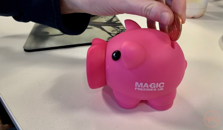 Hand putting 2 pence in pink Magic Freebies piggy bank